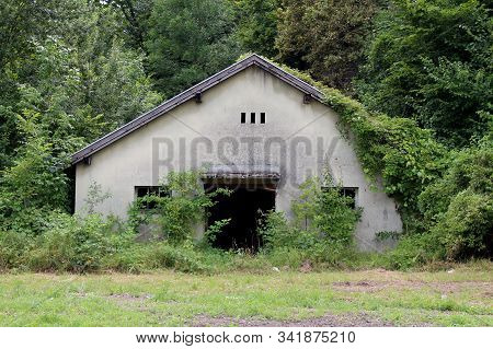 Old dilapidated small military barrack building with broken windows and missing entrance doors completely overgrown with crawler plants and forest vegetation at abandoned military complex stock photo