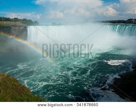 Beautiful rainbow on sunny day over Niagara Falls pool with Horseshow Falls in background. No people or ships visible. Blue sky and clouds over falls. stock photo
