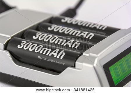 Charger with four 3000mAh batteries. Batteries and charger close up. stock photo