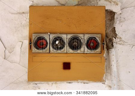 Row of four old vintage retro disconnected ceramic fuse holders with missing fuses on front side of yellow plastic box on dilapidated cracked wall at abandoned military complex building on warm sunny summer day stock photo