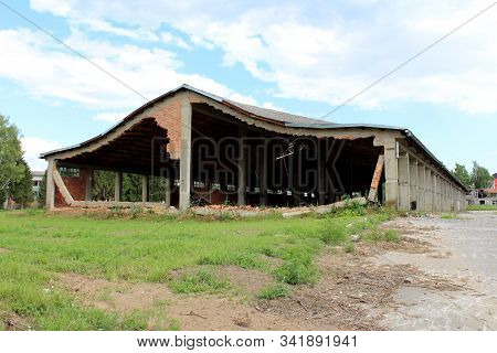Wide large hangar building with missing destroyed red brick support walls and unusual bent roof surrounded with paved area mixed with grass and trees at abandoned military complex on cloudy blue sky background stock photo