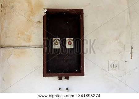 Two old vintage retro disconnected ceramic fuse holders with missing fuses inside wooden box on dilapidated cracked wall next to plastic light switch at abandoned military complex building on warm sunny summer day stock photo