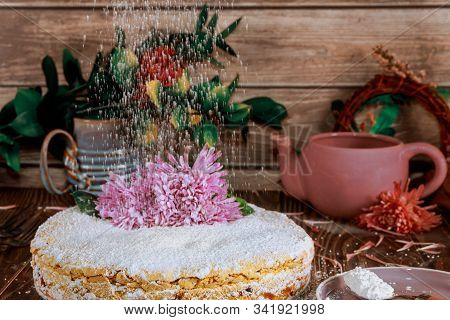 Crumble cake with powdered sugar sprinkles on the top of cake with flowers. stock photo