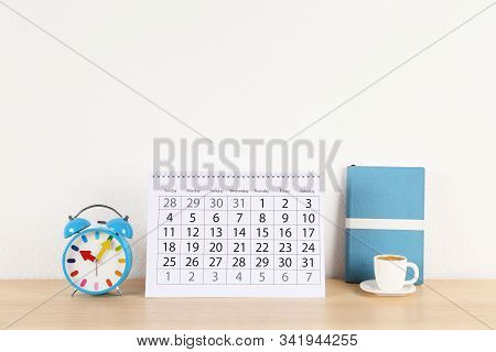 Calendar, alarm clock and cup of coffee on wooden table stock photo