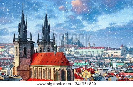 High spires towers of Tyn church in Prague city (Church of Our Lady before Tyn cathedral) urban landscape panorama with red roofs of houses in old town and blue sky with snowfall and clouds. stock photo