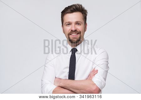 Handsome european businessman in white formal shirt and black tie standing in front of camera stock photo