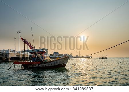 Beautiful seascape sunset with fishing wood boat floating down or park at seaport in asia. stock photo