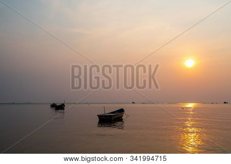 Beautiful seascape sunset with silhouette fishing wood boat floating down or park on sea in asia thailand stock photo