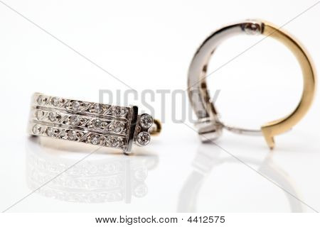 two gold earing with diamonds closeup on white background with reflection stock photo