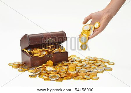 Hand drops money on a heap of chocolate candy euro coins, a treasure chest in the background. stock photo
