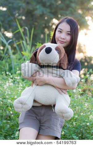 Thai Woman Hug Stuffed Dog On In Grass stock photo