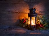Cristmas light in night on old wooden foundation. concentrate on the wick candles