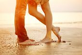 A youthful adoring couple embracing and kissing on the shoreline at nightfall. Two darlings, man and
