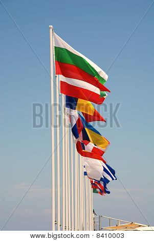 A row of international flags flying at Mandraki harbour on the Greek island of Nisyros. stock photo