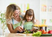 Mother shows little girl cooking on kitchen