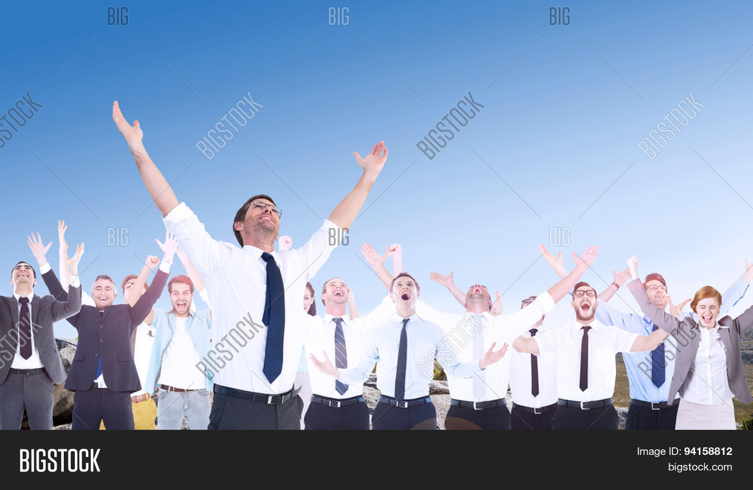 Handsome businessman cheering with arms up against mountain trail