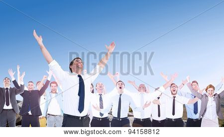 Handsome businessman cheering with arms up against mountain trail stock photo
