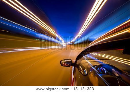 The car moves at great speed at the night. Blured road with lights with car on high speed.