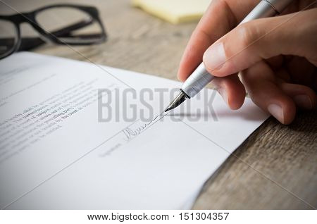Close up of hand of businessman signing a form. Business man signing contract for future deal. Busin