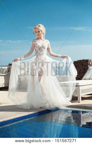 Beauty Portrait of bride wearing in wedding dress with voluminous skirt walking near swimming pool over blue sky outdoor summer photo. stock photo