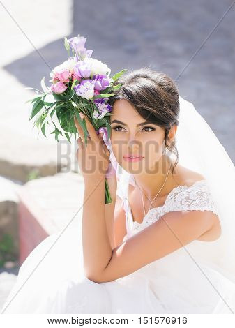 young sexy woman or girl bride with makeup on pretty face and veil in hair holding wedding bouquet or posy of eustoma and rose flowers sunny summer outdoor stock photo