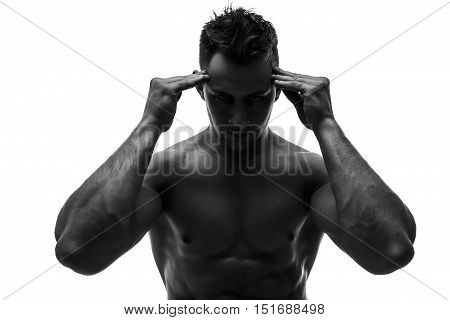 The beautiful and strong young guy holding head with two heands. Pain. Black and white photo, silhouette. Hidden in the shadow.  Male silhouette. stock photo