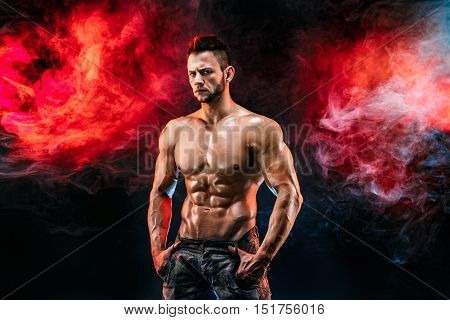 Close up on perfect abs. Strong bodybuilder with six pack. Man with perfect abs, shoulders, biceps, triceps and chest, personal fitness trainer flexing his muscles in blue, red smoke stock photo
