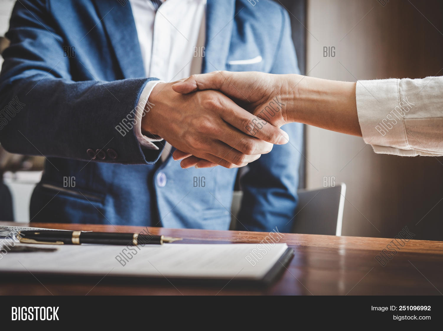 Real Estate Agent And Customers Shaking Hands Together Celebrating Finished Contract After About Hom