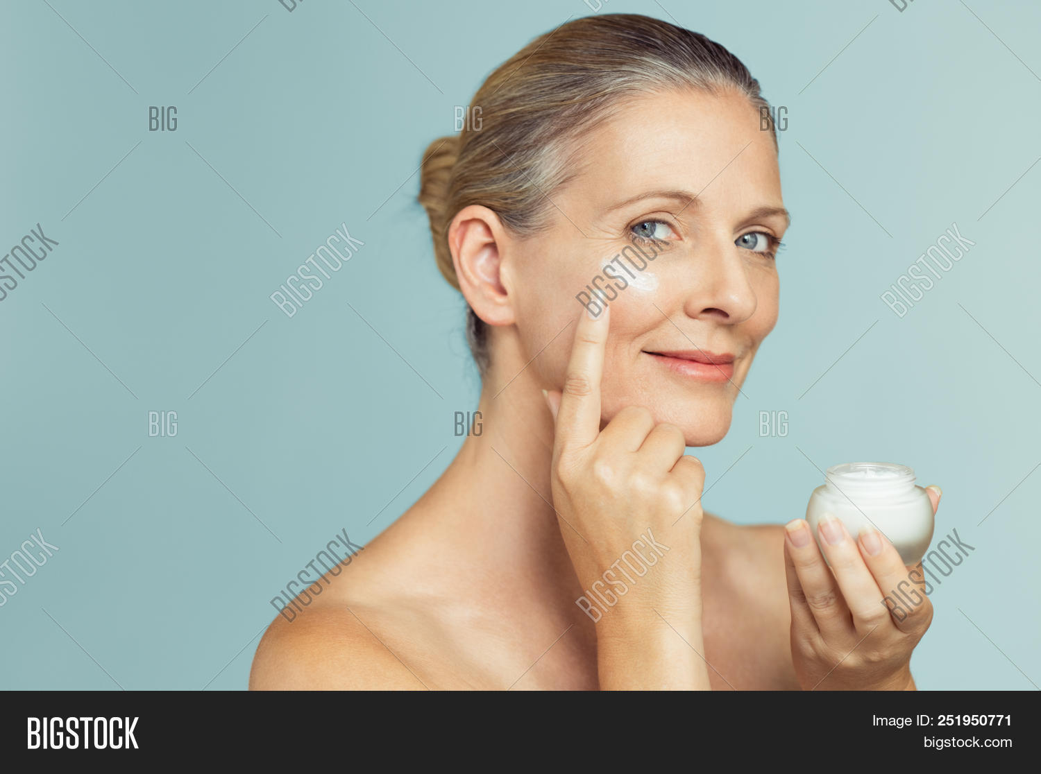 Beautiful mature woman holding jar of skin cream for face isolated on light blue background. Happy s