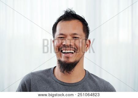 Portrait of laughing young bearded Filipino man stock photo
