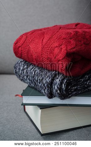 hugge autumn winter concept, red sweaters and books on grey background, cold weather, cozy home stock photo