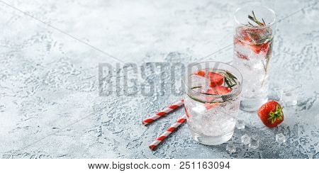 Alcoholic or non-alcoholic cocktail with strawberries and rosemary and ice in glass glasses. Banner Concept stock photo