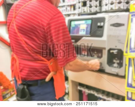 Vintage tone abstract blurred rear view employee operates key duplication machine at hardware store in USA stock photo