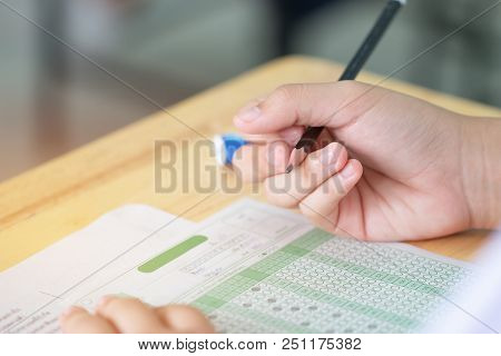 Student taking exams, writing examination on paper answer sheet optical form of standardized test on desk doing final exam in classroom, Examination sitting on row chair in school. stock photo