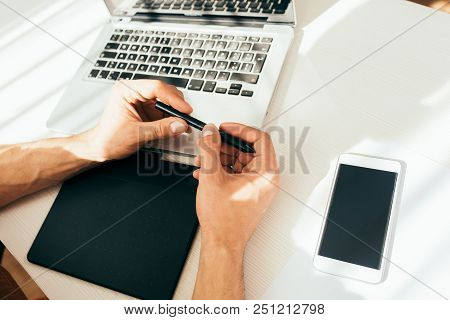Technology composition, top view shot of gadgets. Handsome hands of man with digital pen next to the laptop computer with blank screen. Working process with digital pen and tablet. Technology concept stock photo