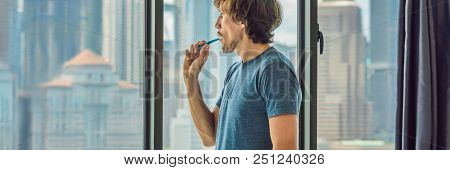 Young man brushing his teeth in his bathroom. BANNER, long format stock photo