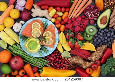 Food for good heart health with fresh fish, fruit, vegetables, herbs, nuts and olive oil. Super food