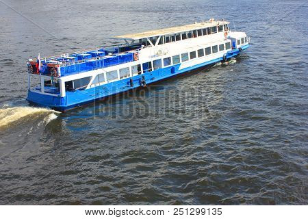 Cruise Excursion Tour Boat on River Canal Water. Outdoor Summer Day View of Cruise Ship with Passengers for Guided River Tours in the City Center, Top View with Water Background and Empty Copy Space. stock photo