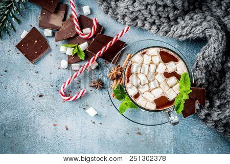 Homemade hot chocolate with mint, candy cane and marshmallow, light blue background with warm blanket, copy space stock photo