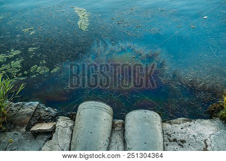 Sewer Pipes At Shore, Stain Of Oil Or Fuel On Water Surface, Nature Pollution By Toxic Chemicals, Di