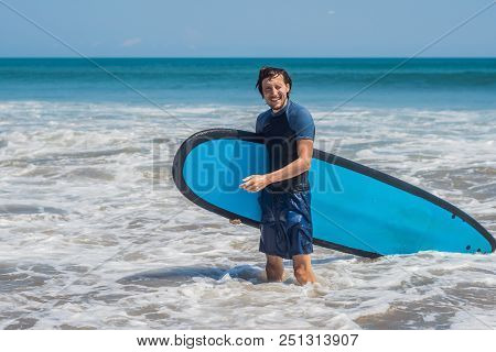 Young man, beginner Surfer learns to surf on a sea foam on the Bali island. stock photo