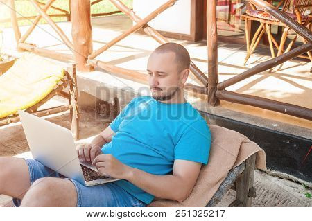 A man sitting on a wicker lounge chair and working at the computer. The concept of remote work stock photo