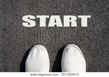 Two white sneakers on black asphalt. The inscription START. View from above. Copy space. Backgrounds. stock photo