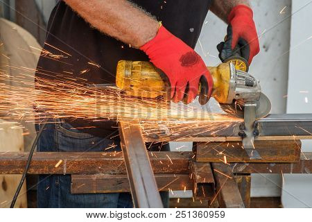 men working with hand grinder on metal construction stock photo