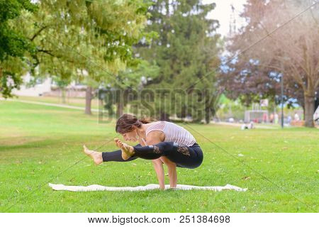 Strong supple woman working out in a park balancing on her hands with outstretched legs in the air in side view in a health and fitness concept stock photo