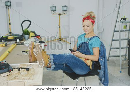 Beautiful young female in jeans overalls and red headband sitting relaxed with legs on desk with tools and using mobile phone in hand stock photo