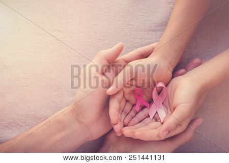 Adult and child hands holding pink ribbons, Breast cancer awareness, abdominal cancer awareness and October Pink background stock photo