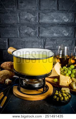 Gourmet Swiss fondue in traditional fondue pot, with forks, various cheeses, olives, bread and grape, dark blue background copy space stock photo