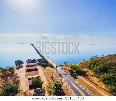 Aerial top view of a long highway bridge above a river. Highway on horizontal, isolated by the green water of the river. Bridge Helio Serejo over the Parana river, Brazil. stock photo