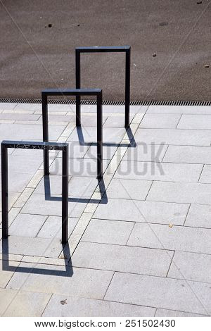 Modern and in a row arranged angular bicycle stands cast shadows on the asphalt. stock photo